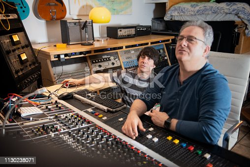 Musician and sound engineer at mixing console using music editing software to analyz3, mix and master analog recording to digital.  Vancouver, British Columbia, Canada