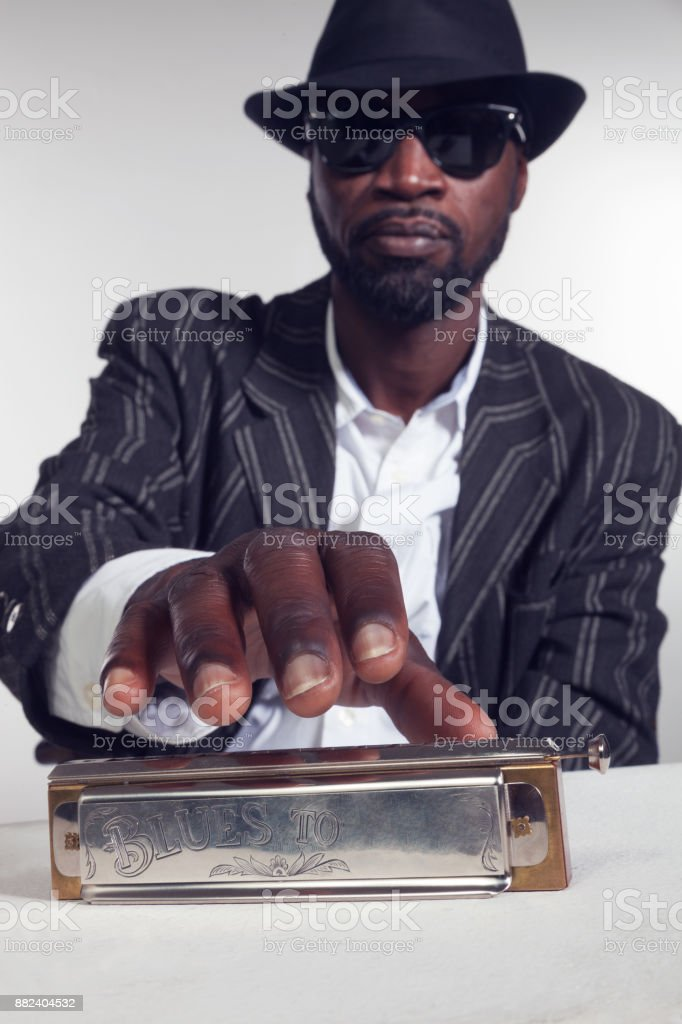 Musician takes the harmonica in the foreground stock photo