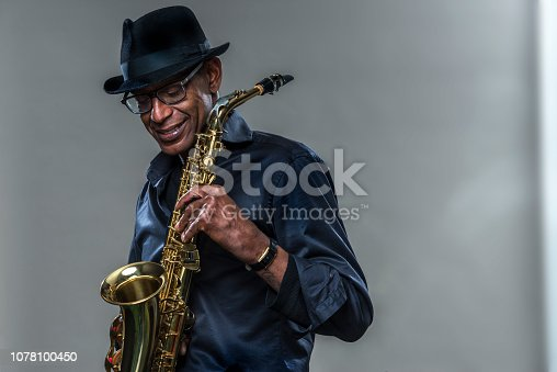 Musician with saxophone  against a grey backdrop. Man looking downwith a smile, wearing a black hat and shirt