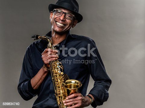 Musician with saxophone  against a grey backdrop. Man looking at camera with a smile, wearing a black hat and shirt