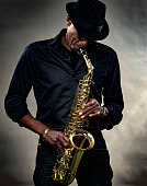 Musician with saxophone against a gray backdrop. Men plays the saxophone, wearing a black hat and clothes