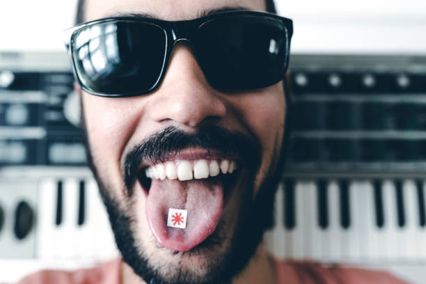 Musician With Synthesizer Showing LSD On His Tongue Musician With Synthesizer Showing LSD On His Tongue acid stock pictures, royalty-free photos & images