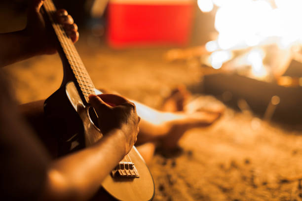 A musician woman playing ukulele guitar next to a campfire on the beach. stock photo