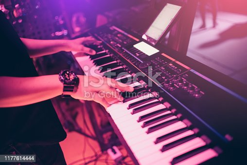Musicians are playing keyboards in concert.