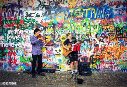 Prague, Czech Republic - July 25, 2013: Two young musicians playing at John Lennon wall. The wall is filled with John Lennon-inspired graffiti and pieces of lyrics from Beatles songs.