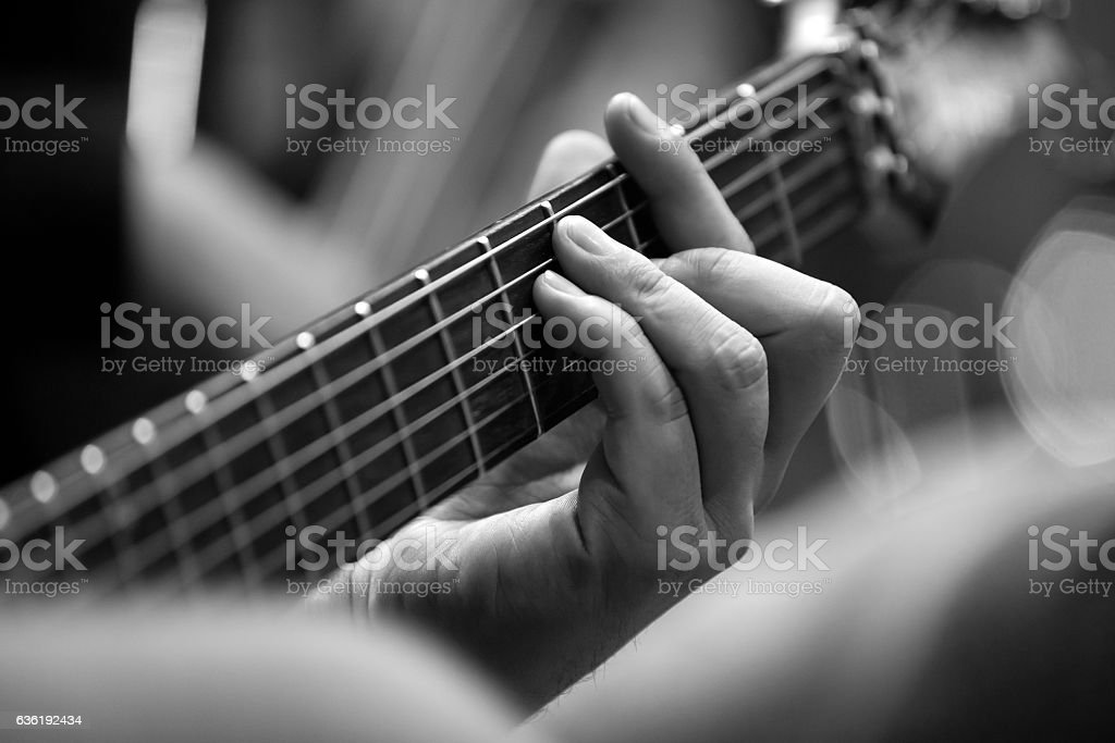 Musician's fingers on the strings of a guitar closeup stock photo