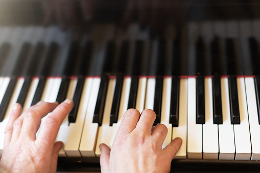 Musician's hands playing a magnficent grand piano keyboard