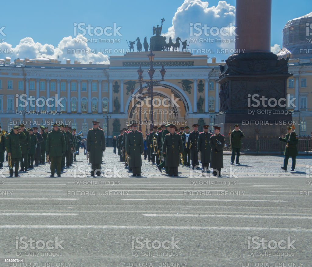 musicians of a military brass band is preparing for the rehearsal of the victory parade on the background of the headquarters ' arch stock photo