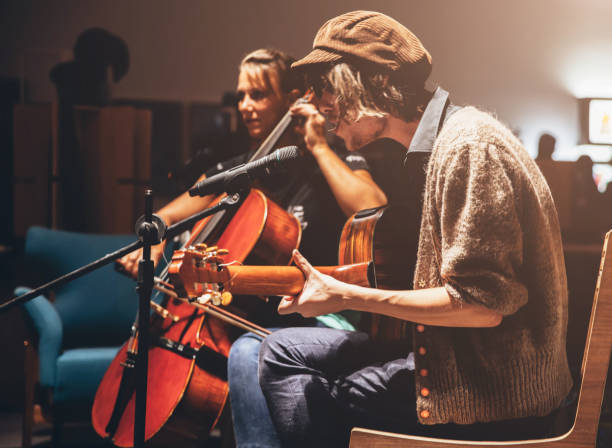 Musicians on A Stage Two musicians on a stage performing. folk music stock pictures, royalty-free photos & images