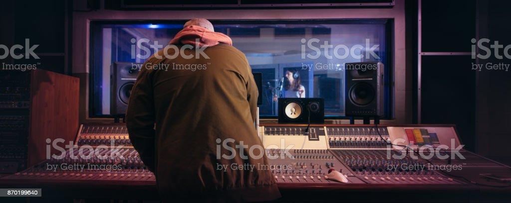 Musicians producing music in professional recording studio stock photo