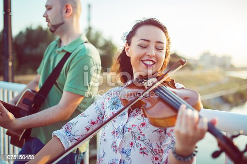 Virtuous duo with violin and guitar performing on the bridge