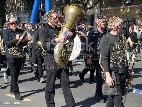 Rijeka, Croatia, March 3rd, 2019. Group of musicians with one with big trumpet instrument in the center, walking on the carnival parade