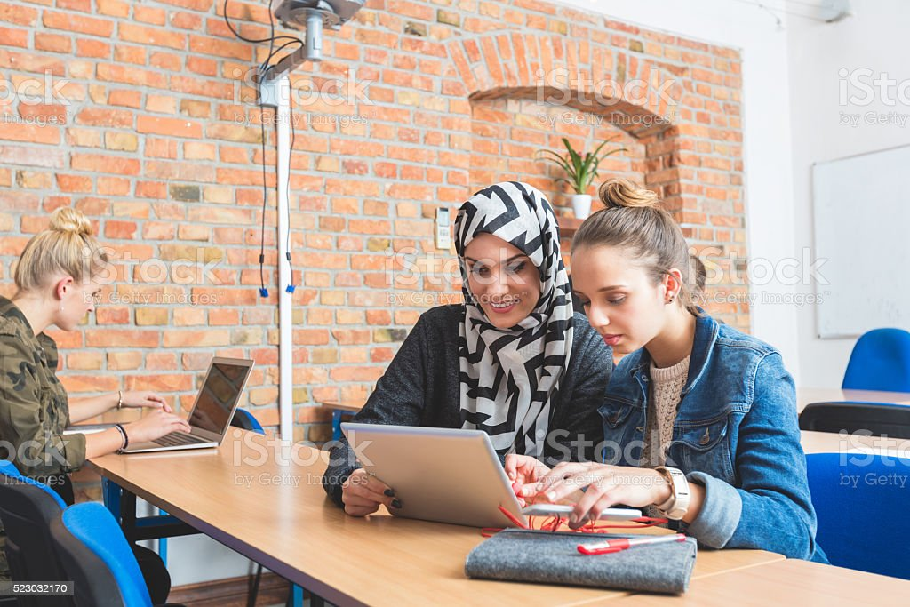 Musilm young woman working on laptop with friend stock photo