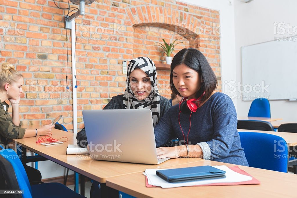 Musilm young woman working on laptop with her asian friend Musilm female student working on laptop with her asian friend at the university. Achievement Stock Photo