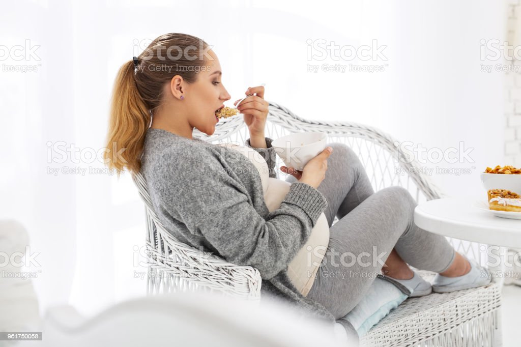 Musing pregnant woman swallowing granola royalty-free stock photo