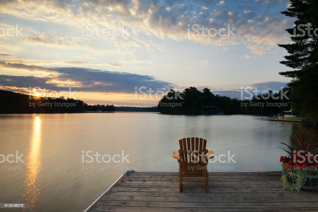 Muskoka chair on a dock at sunrise stock photo