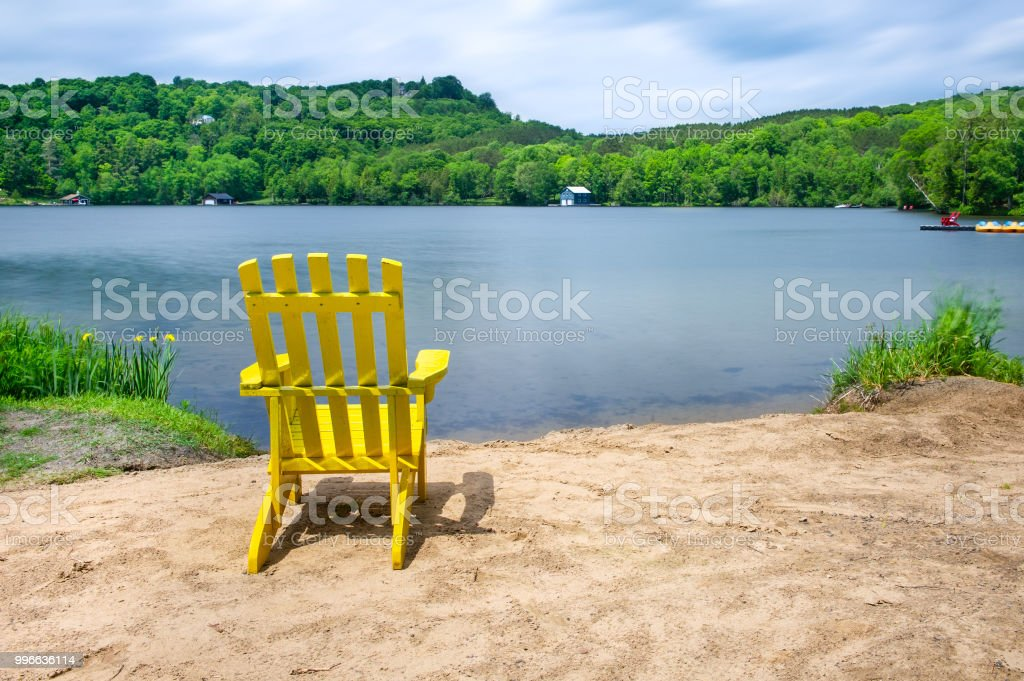 Muskoka chair on a sandy beach stock photo