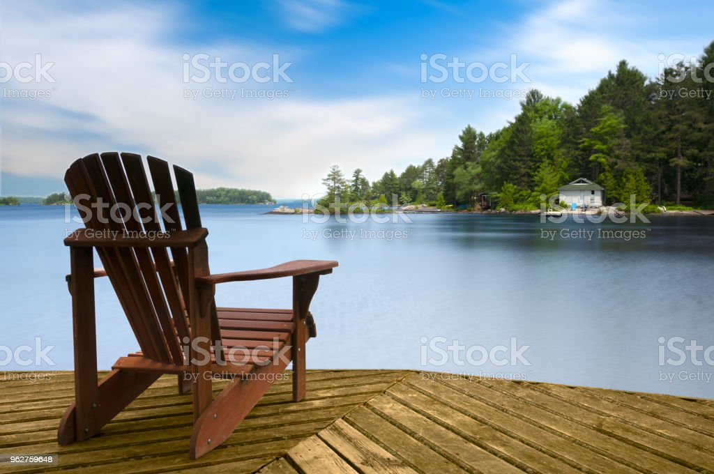 Muskoka chair on a wooden dock stock photo