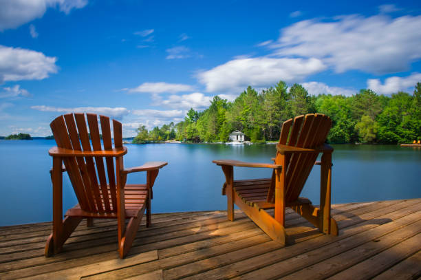 Muskoka chairs on a dock facing a lake stock photo
