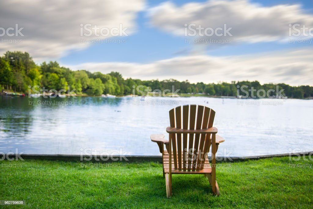 Muskoka chairs on a green lawn stock photo