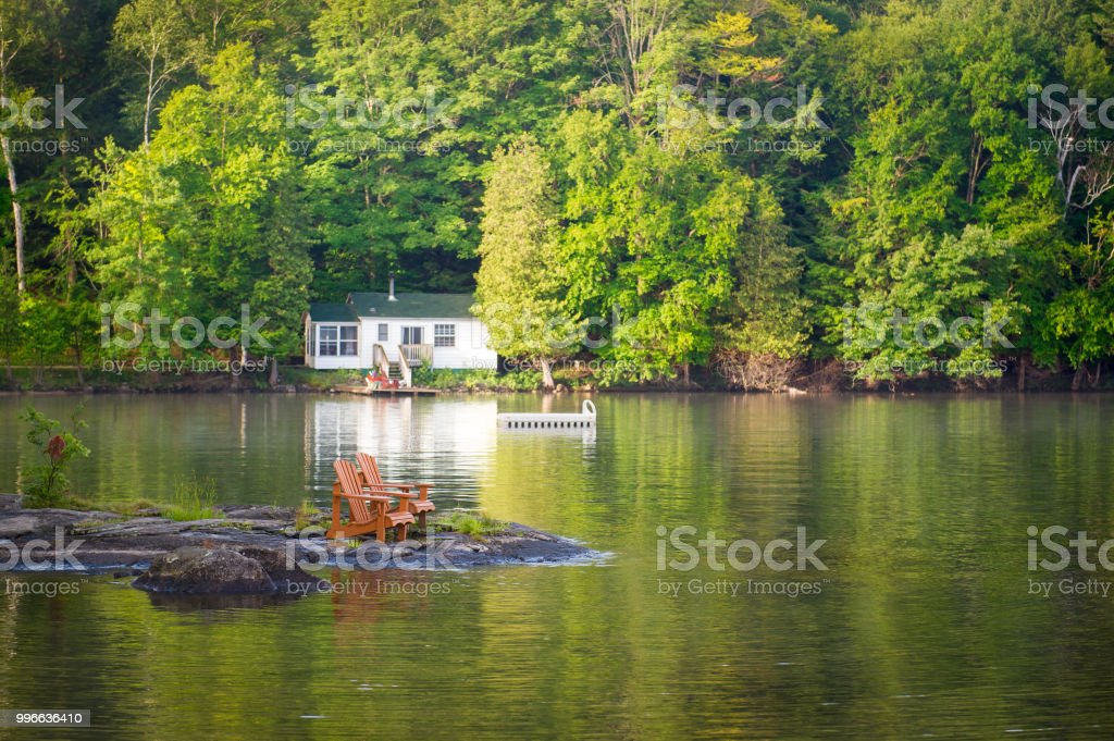 Muskoka chairs on a rock formation facing calm waters stock photo