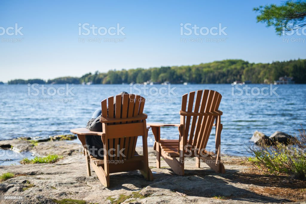 Muskoka chairs on a rock formation stock photo