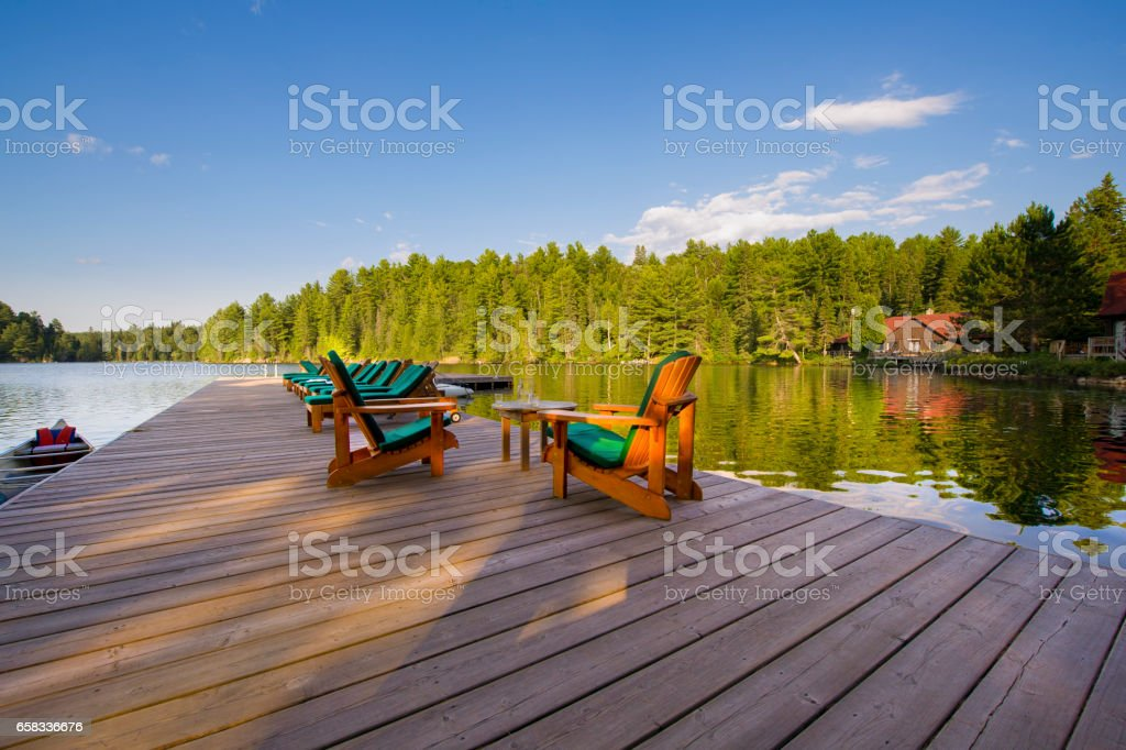 Muskoka chairs on a wood deck stock photo