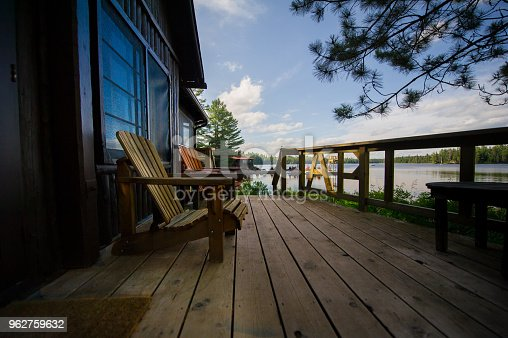 Two Muskoka chairs on a wooden deck facing a lake. In the background there's a pier with a big amount of chairs