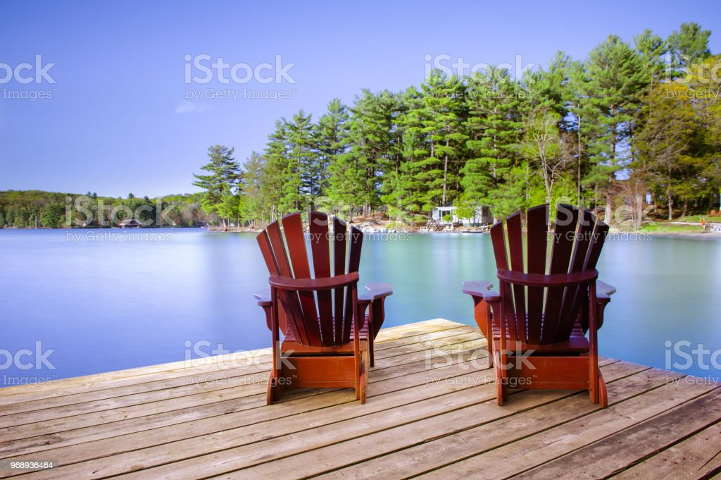 Muskoka chairs on a wooden dock facing calm water stock photo