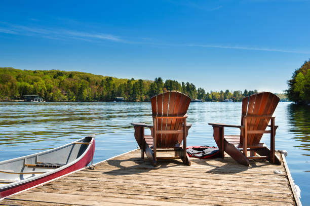 Muskoka chairs on a wooden dock Two Muskoka chairs on a wooden dock overlooking the blue water of a lake in Muskoka, Ontario Canada. A red canoe is tied to the pier and life jackets are visible near the chairs. lake stock pictures, royalty-free photos & images