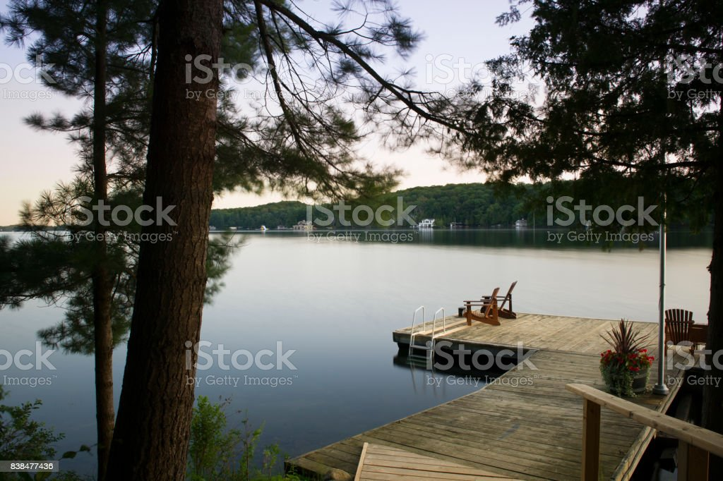 Muskoka chairs on a wooden dock stock photo