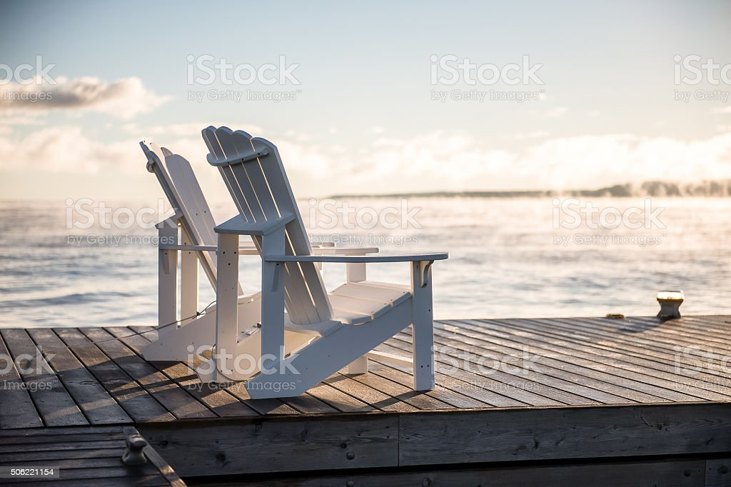 Muskoka chairs on the dock high key stock photo