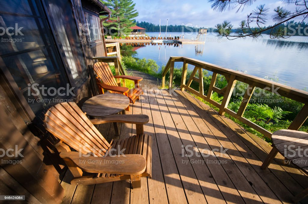 Muskoka chairs sitting on a wooden porch stock photo