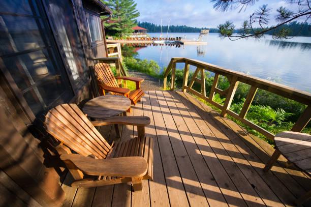 muskoka sandalye ahşap bir verandada oturup - kır evi stok fotoğraflar ve resimler