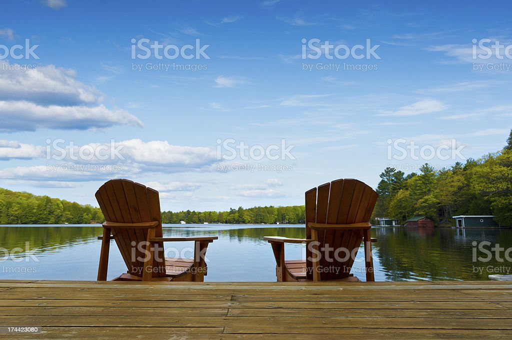 Muskoka chairs sitting on dock facing calm lake stock photo