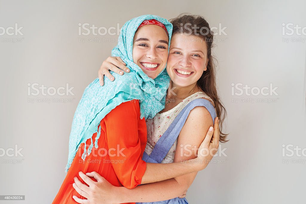 muslim and christian girl hugging each other stock photo