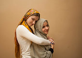 Friendship of the religions concept: muslim and christian girl together