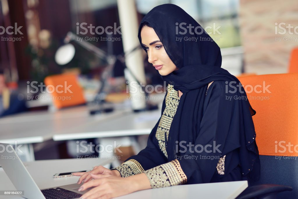 Muslim asian woman working in office with laptop stock photo