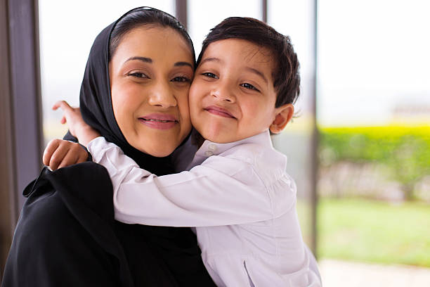 muslim boy hugging his mother stock photo