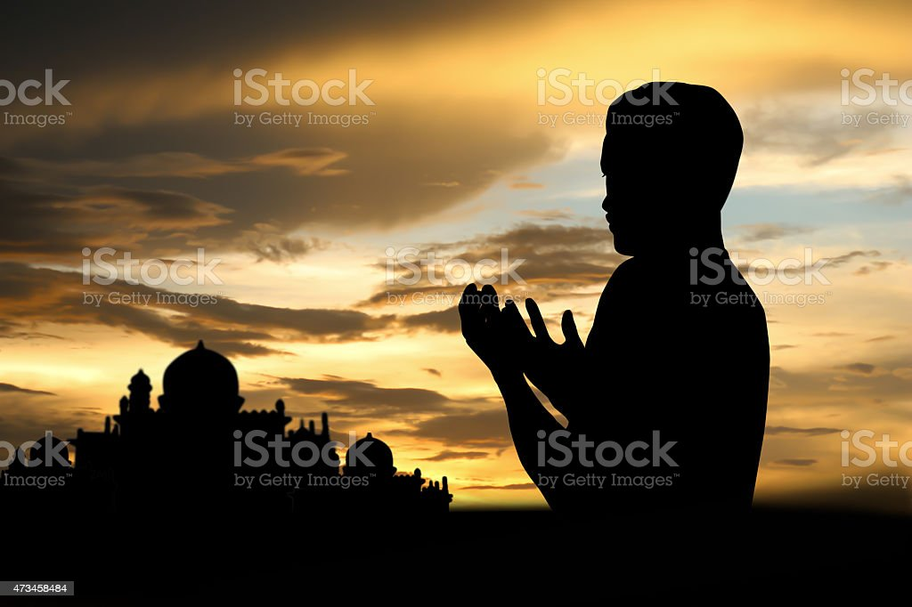 A Muslim boy in prayer at sunset stock photo