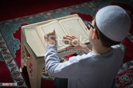Muslim boy reading The Holy Koran in Mosque