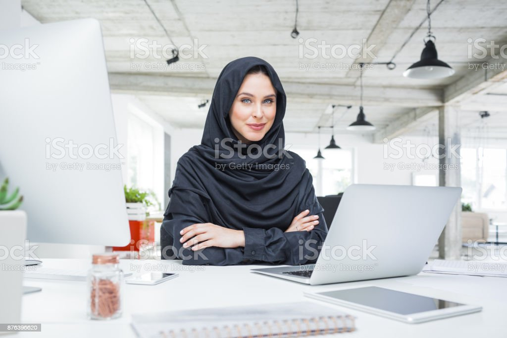 Muslim business woman at work in modern office Muslim female sitting at her desk with laptop computer and looking at camera. Business woman at work in modern office. Adult Stock Photo