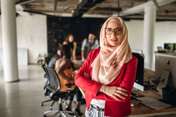 Muslim business woman in a conference room Portrait of a young Arabic business woman standing in the modern office religious veil stock pictures, royalty-free photos & images