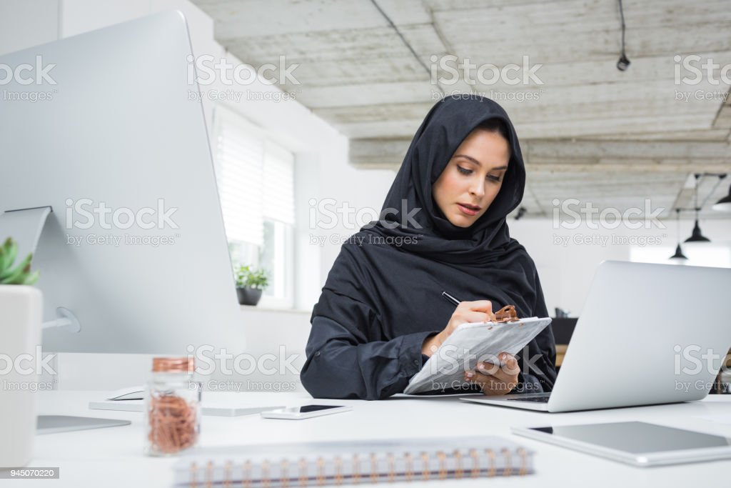 Muslim business woman working in office Business woman working on her laptop in the office. Muslim female in head scarf sitting at her desk using laptop computer. Adult Stock Photo