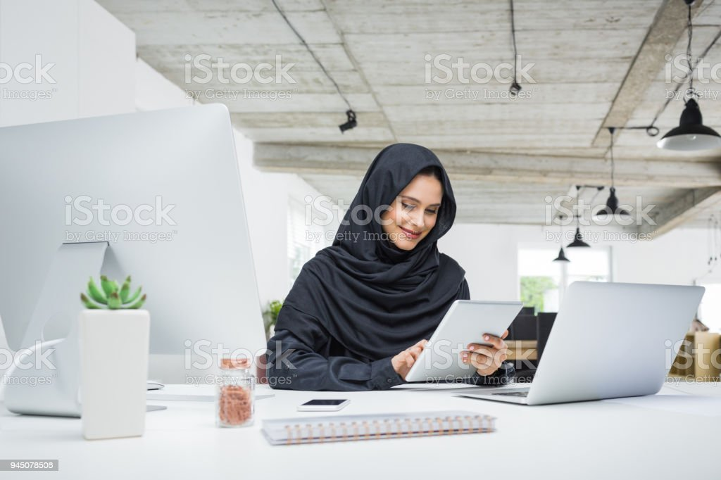 Muslim business woman working in office Smiling business woman working on her laptop in the office. Muslim female in head scarf sitting at her desk using digital tablet and laptop computer. Adult Stock Photo