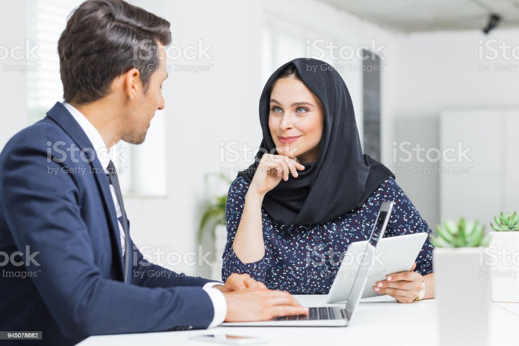 Muslim businesswoman in discussion with colleague Muslim businesswoman holding digital tablet and discussing work with businessman in office. Businesspeople discussing new project. 20-29 Years Stock Photo