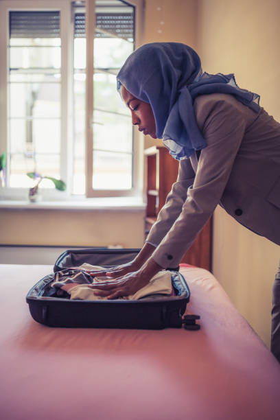 a muslim businesswoman packing a suitcase in a hotel room - donna valigia solitudine foto e immagini stock