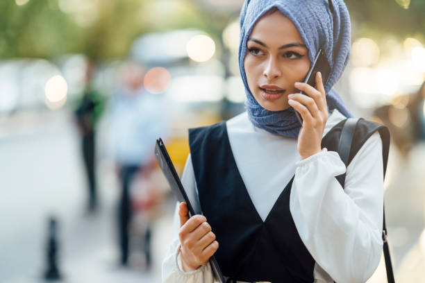 Muslim businesswoman talking on phone ain street A Muslim businesswoman is talking on the phone in the street. arabic style stock pictures, royalty-free photos & images