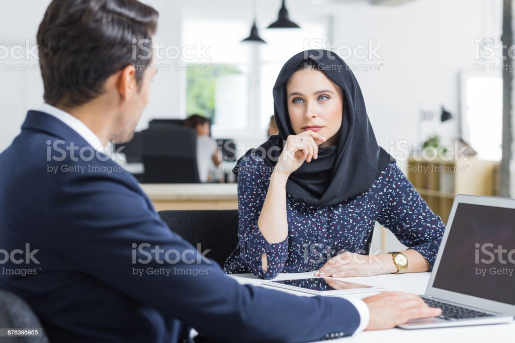 Muslim businesswoman working listening to male colleague in office Muslim businesswoman sitting at table and listening to male colleague. Professional employees discussing ideas for new business project in office. 20-29 Years Stock Photo