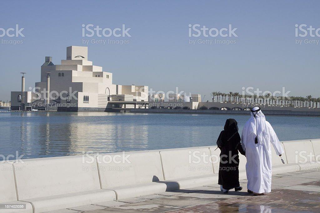 Muslim couple along Doha Corniche stock photo